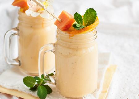 Homemade smoothie with tropical fruits: mango, banana, pineapple, papaya in glass Mason jar. Healthy juicy vitamin drink