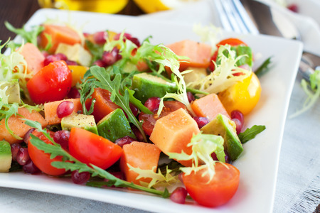 Ripe papaya and avocado salad with cherry tomatoes and pomegranate seeds. Healthy lunch