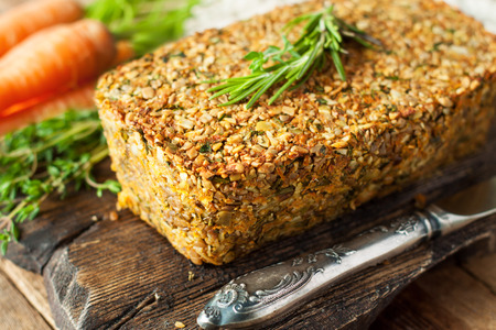Vegetarian pate in shape of meatloaf served with fresh herbs and cherry tomatoes. Healthy homemade food
