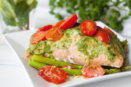 Salmon baked in foil with pesto sauce, cherry tomatoes and asparagus. Delicious healthy seafood dinner