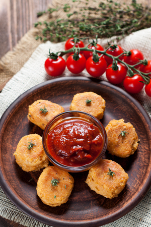 Homemade fried fish croquettes from canned salmon, egg yolks, onion, coconut butter and spices, served with tomato sauce and cherry tomatoes