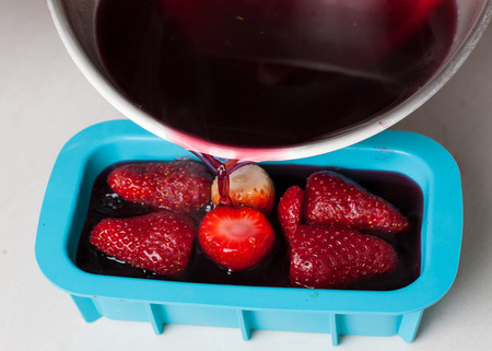 Preparation of fruit jelly terrine with berries. Pouring hibiscus and gelatin liquid in pan with berries