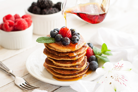 Stack of delicious paleo apple-cinnamon pancakes served with fresh berries, mint and maple syrup