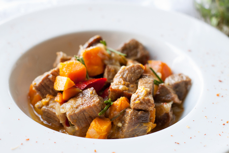 Beef stew with butternut squash, pepper and onion decorated with fresh rosemary in white plate on marble table Standard-Bild