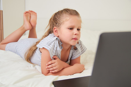 Little blonde girl looking at laptop while lying on bed in her room