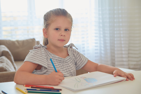 Cute little girl drawing in pencil in drawing book at home