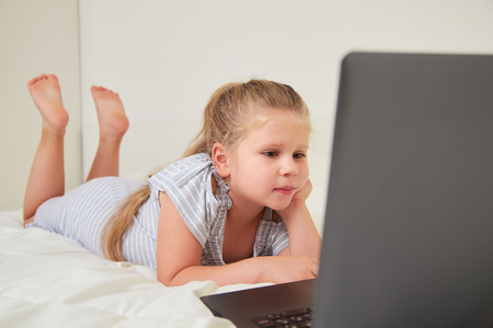 Cute little girl lying on bed at home, watching cartoons on laptop
