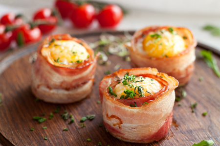 Tasty egg muffins wrapped in crispy bacon on round wooden serving board garnished with greens and cherry tomatoes