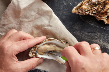 View of male hands shucking fresh oyster, view from above