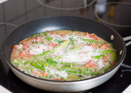 Preparation of frittata with smoked trout and asparagus, frying on pan