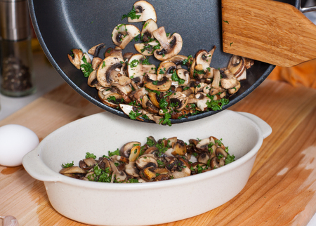 Cooking baked eggs with mushrooms. Put fried mushrooms with greens in baking dish 스톡 콘텐츠 - 113955744