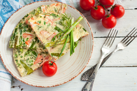 Homemade frittata with smoked trout and asparagus served with fresh cherry tomatoes