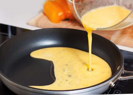 Preparation of Mexican chicken omelet. Pouring beaten eggs on hot frying pan with oil 스톡 콘텐츠