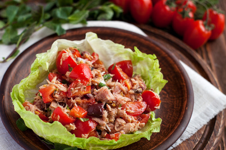 Healthy appetizers lettuce wraps with canned tuna, bell pepper, herbs on clay plate
