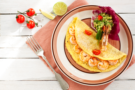 Omelette with shrimps, cheese and avocado and shrimp salsa served with cherry tomatoes