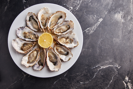 Fresh open oysters served with lemon slices on white plate on black marble table