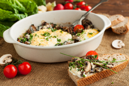 Delicious baked eggs with mushrooms served in baking dish with slice of wholemeal bread and cherry tomatoes
