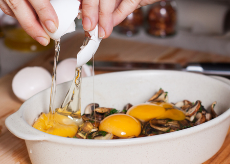 Preparation of baked eggs with mushrooms. Female hands pouring broken raw chicken eggs on fried mushrooms in baking dish 스톡 콘텐츠