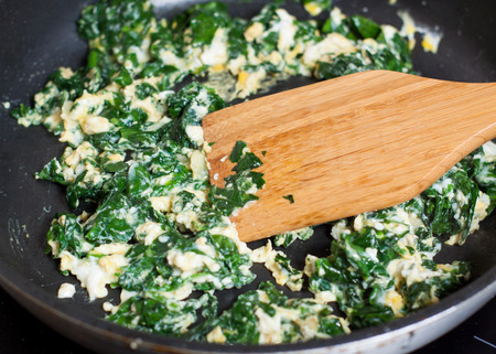 Preparation of scrambled eggs with spinach - adding egg to spinach leaves 스톡 콘텐츠 - 113954254