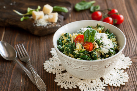 Bowl with scrambled eggs with spinach on wooden table, healthy breakfast