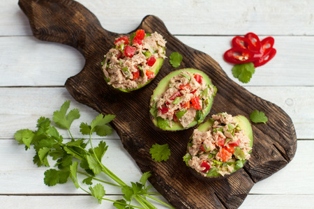 Avocado appetizers stuffed with canned tuna, bell pepper, herbs on wooden cutting board