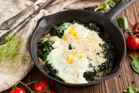 Healthy breakfast, fried eggs with spinach in frying pan on wooden table 写真素材