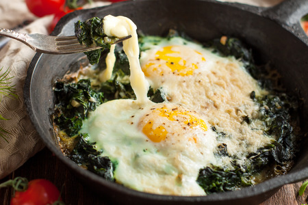 Healthy breakfast, fried eggs with spinach in frying pan on wooden table 스톡 콘텐츠 - 113954196