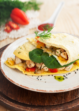 Delicious Mexican omelette with filling of fried chicken fillet, bell peppers and onion garnished with greens on wooden background