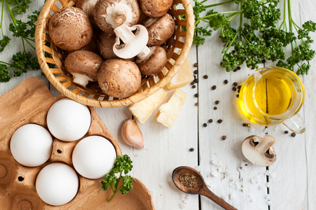 Raw eggs, fresh brown crimini mushrooms, Parmesan cheese, olive oil, parsley and spices on wooden background. Ingredients for baking eggs with mushrooms 스톡 콘텐츠