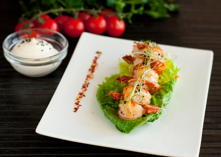 Tiger shrimps grilled with garlic and spices served on romaine lettuce salad leaf 스톡 콘텐츠 - 113954199