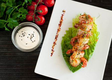 Tiger shrimps grilled with garlic and spices served on romaine lettuce salad leaf 스톡 콘텐츠 - 113954200