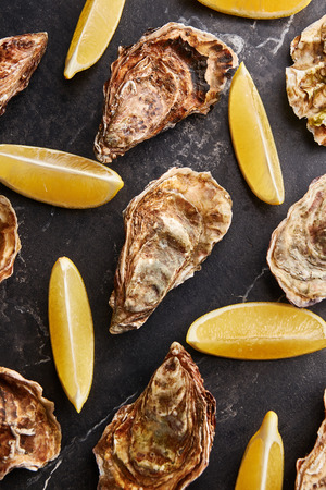 Seafood pattern of wild Netherlands oysters and fresh lemon slices on black marble background, top view