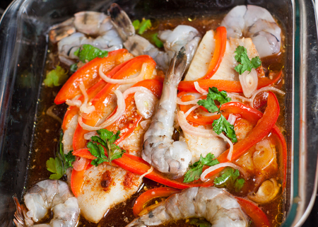 Preparation of healthy seafood dish - tilapia fillets baked with shrimps and vegetables. Raw ingredients in cooking tray