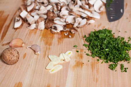 Chopped champignons, parsley and garlic on wooden cutting board. Preparation of baked eggs with mushrooms 스톡 콘텐츠 - 113954206