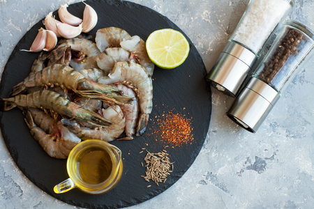 Raw ingredients for seafood dish - tiger shrimps, olive oil, garlic and lemon, spices