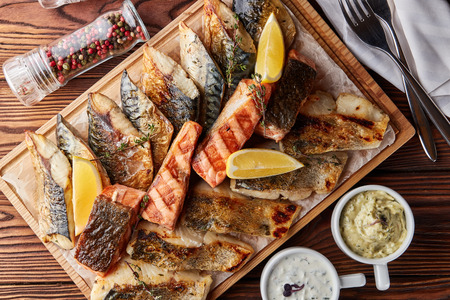 Assorted grilled fish fillets served with lemon slices and thyme on wooden cutting board