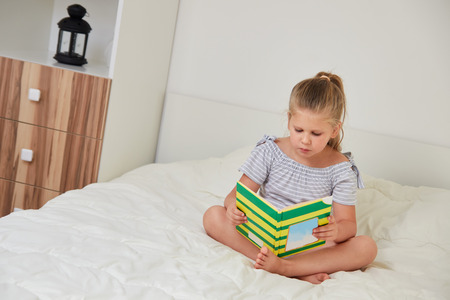 Cute little girl sitting on bed at home and reading book with fairy tales