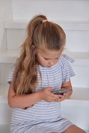Portrait of little blonde girl absorbedly looking at phone while sitting on staircase indoors