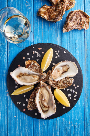 Fine de claire oysters served with lemon slices and glass of white wine on blue wooden table Stock Photo