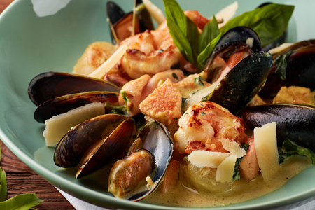Assorted seafood, mussels, squid, scallops, salmon fillet and tiger shrimps with garlic creamy sauce, parmesan cheese and basil Standard-Bild