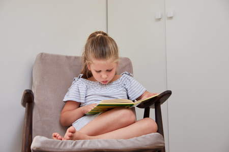 Cute little girl sitting in cushioned armchair at home and reading book with fairy tales
