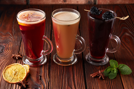 Three glasses with hot alcoholic drinks - mulled wine, punch and apple cider cocktail with orange, cinnamon, cloves and star anise on dark wooden table