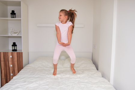 Cheerful cute little girl jumping on bed while having fun at home 스톡 콘텐츠
