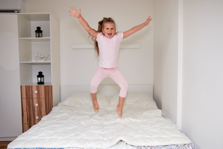 Happy little blonde girl having fun at home, playing and jumping on bed 스톡 콘텐츠