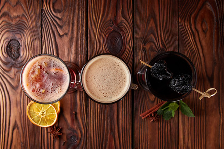 Three glasses with hot alcoholic drinks - mulled wine, punch and apple cider cocktail with orange, cinnamon, cloves and star anise on dark wooden table, view from above