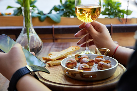 Girl sitting in outdoor cafe enjoying escargot snails with herbs butter and white wine and using phone 스톡 콘텐츠 - 122762704