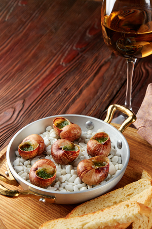 Escargot snails with garlic herbs butter in aluminum pan on rustic wooden background 스톡 콘텐츠 - 122762699