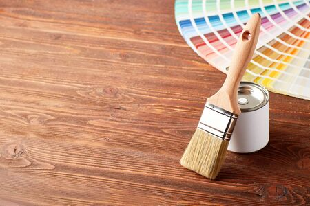 Painting brush, closed can with paint, color guide palette on wooden table with copyspace. 스톡 콘텐츠