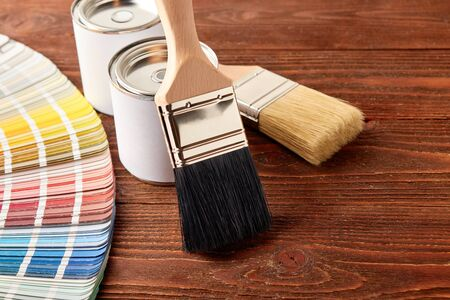 Two painting brushes, cans with paint, color guide palette on wooden table.