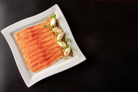 Sliced smoked or salted salmon served on white square plate with cream cheese, pistachios and greens on black background, top view 스톡 콘텐츠